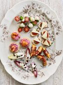 Various appetisers on a floral patterned plate (seen from above)