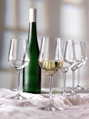 A glass of white wine, a bottle of wine and empty glasses