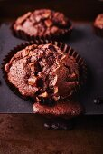 Dark chocolate muffins in a baking tin with the mixture spilling over the edge