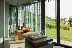 Wine glasses on a large wooden table in front of floor-to-ceiling windows in a vinotheque; Weingut am Stein, Würzburg