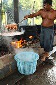A man cooking prawns, Thailand