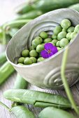 A bowl of peas with purple flower
