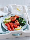 A healthy breakfast of salmon, tomatoes, spinach and avocado
