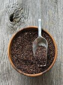 Black quinoa in a wooden bowl with a scoop