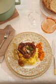 And elegant place setting with veal knuckle in wine and lemons on polenta, main course