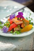 Fruity salmon salad with oranges, grapefruit and edible flowers