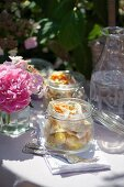 Potato salad with chicken and vegetable strips in preserving jars for picnic