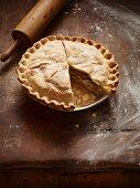 Angeschnittene Apple Pie auf altem Holzküchentisch mit Nudelholz