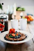 Chocolate cake with fresh blueberries and strawberries on a plate with white cups and a cafetière in the background