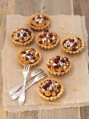 Shortbread tartlets with poppyseeds, toffee cream, cranberries and hazelnuts