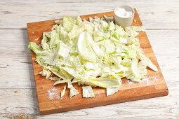 Sliced Chinese cabbage with salt on a chopping board