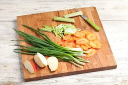 Sliced vegetables and apples on a chopping board