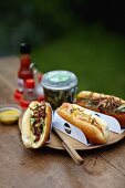 Three different hotdogs on a picnic table