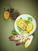 Gerollte Kartoffelmatte auf Chicoree-Frisee-Salat