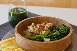Rice noodles with broccolini and a glass of smoothie with blueberries, spirulina, cabbage, spinach, rice milk and bananas
