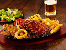 A mixed grill platter featuring chicken, spare ribs, chips and beer