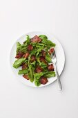 Rocket salad with a vinegar and oil dressing and fried bacon