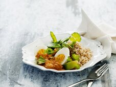 Indian curry with boiled eggs, dried apricots, rice and sugar snap peas