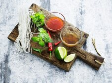 Glass noodles, herbs and sauces for Asian cuisine on a wooden board
