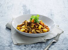 Vegetable stew with beef, mushrooms and pasta on a plate