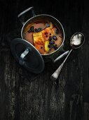Fish soup with black olives in a pot