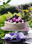 Meringue cake with cherries and rose petals