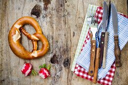 A pretzel, radishes and rustic cutlery (seen from above)