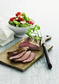 Sliced roast beef with a radish and vegetable salad