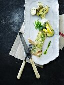 Baked fish with herb cream, potatoes and courgette