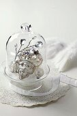 Silver Christmas decorations under glass cover