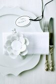 White place setting with china flower and tag labelled 'Bon appétit'