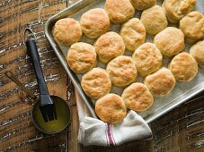 Buttermilk biscuits on a baking tray with melted butter and a baker's brush