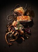 Grilled octopus on a brown metal surface, stuffed and sliced with kitchen twine, roasted pine nuts, paprika power, red onions and sage