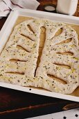 Unbaked fougasse with bacon and walnuts on a baking tray