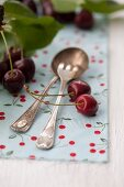 Silver cutlery with cherries and cherry leaves