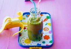 A banana and pear smoothie with dates, lettuce and carrots leaves