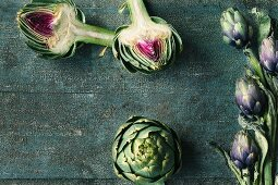 Fresh artichokes, whole and halved, on a wooden surface