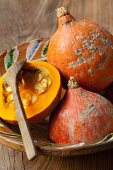 Pumpkins, whole and halved, in a ceramic bowl