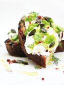 Bruschetta topped with ricotta, broad beans and pumpkin seeds