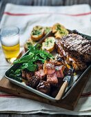 Grilled marinated beef steaks with garlic bread, salad and beer