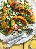A salad with roasted sweet potatoes, green beans, feta cheese and red onions
