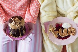 Pancake letters in berry sauce and brownie flapjacks with peanut butter sauce and salted pretzels