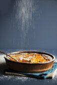 Apricot clafoutis being dusted with icing sugar