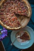 A pecan nut tart, sliced, on a cake stand