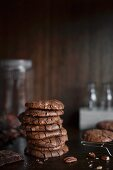 A stack of chocolate and pecan cookies with a various bottles in the background