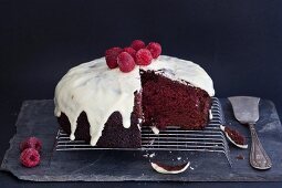 A Red Velvet cake with icing sugar and raspberries on a wire rack (sliced)