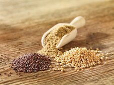 Various mustard seeds on a wooden surface
