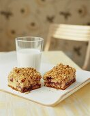 Two slices of sour cream crumble cake with redcurrant jam in front of a glass of milk