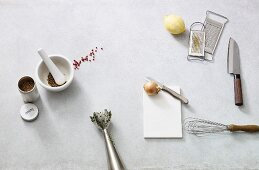 Various kitchen utensils, a lemon, an onion and spices