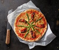 Pizza Margherita with asparagus and aubergines on a piece of paper with a knife
